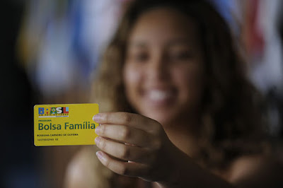 Mulher segurando cartão Bolsa Família