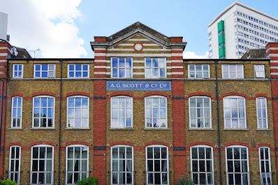 Photograph showing a wider view of the building. The top three storeys are visible: the higher strorey has small rectangular windows and striped brickwork while the lower storeys have large rectangular windows with curved tops.  The tiled sign is at the centre, and this central section has a triangular pediment with the same striped brickwork as the top storey.