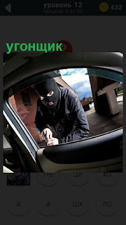 угонщик в маске пытается взломать дверку машины