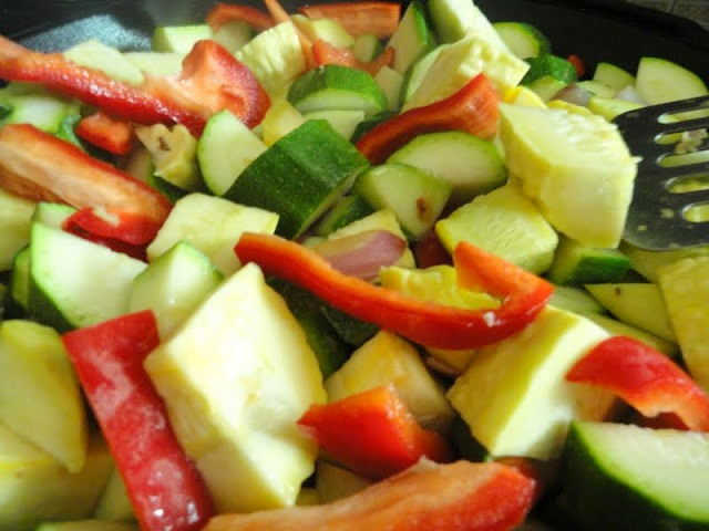 Zucchini, Summer Squash, Red Bell Pepper and Garlic added to Red Onions in cast iron pan.