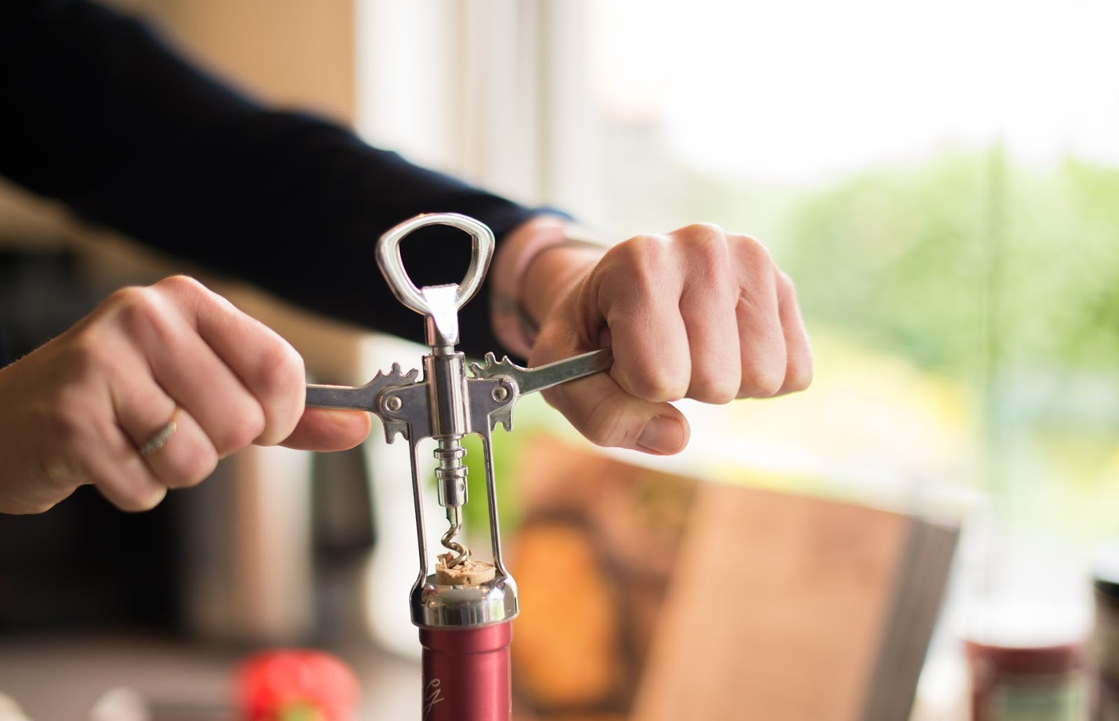 woman using  a corkscrew to open a bottle of wine