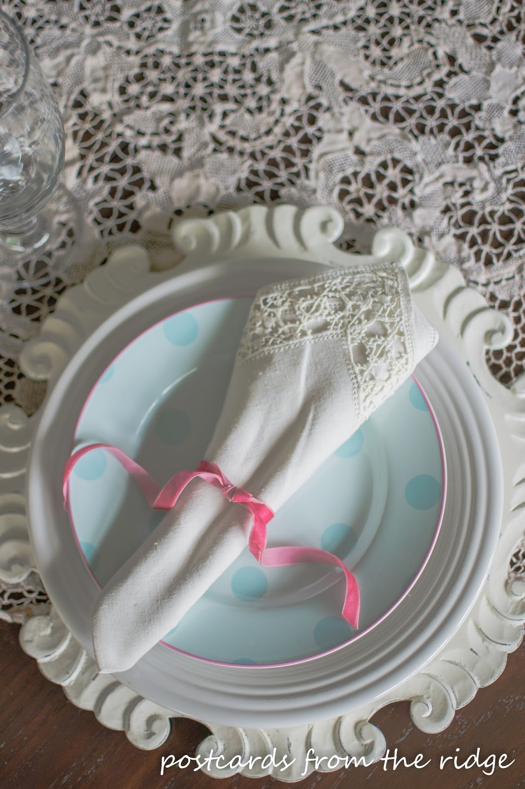 Spring table decor using vintage lace, pastel dishes, and velvet ribbon. Postcards from the Ridge