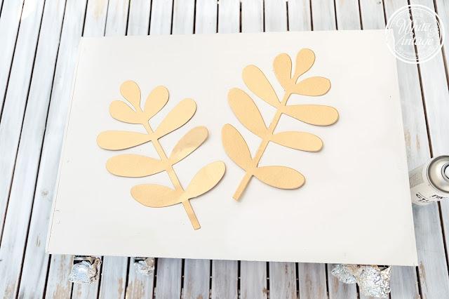 Blattmotiv mit Chalkpaint-Spray auf Holzkiste sprühen.