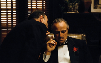 "Don Corleone (Marlon Brando) receives some news from an associate in Francis Ford Coppola's film ""The Godfather."""