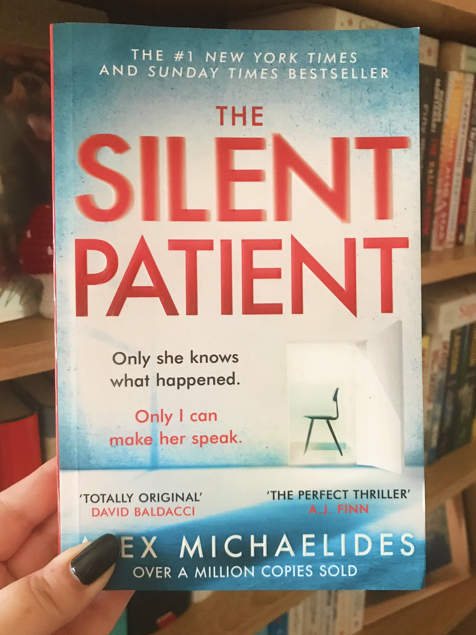 The Silent Patient by Alex Michaelides held up in front of bookshelf