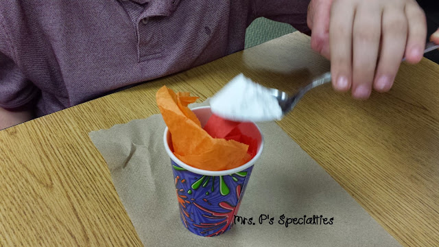 photo of student spooning baking soda into the cup