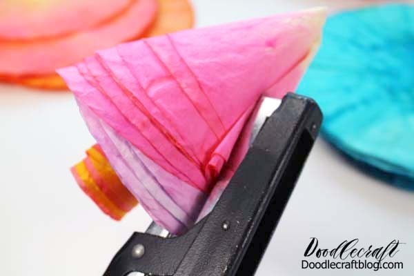 How to make a rose out of coffee filters dyed with food coloring bright colors, stapled together in layers.