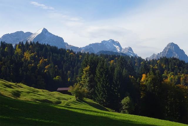 Wettersteingebirge mit schneebedeckten Bergspitzen, grüne Hügeln, braune Holzhütte und Wald