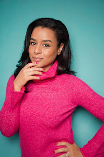 Sarah Cooper in a pink sweater against a blue background