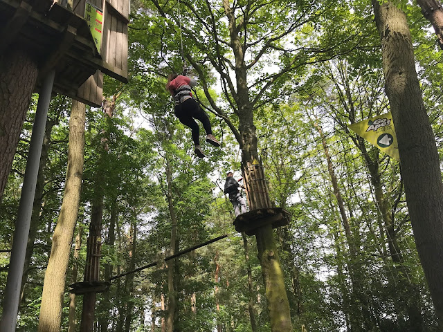 daughter on a zip line into a cargo net in the trees go ape matfen
