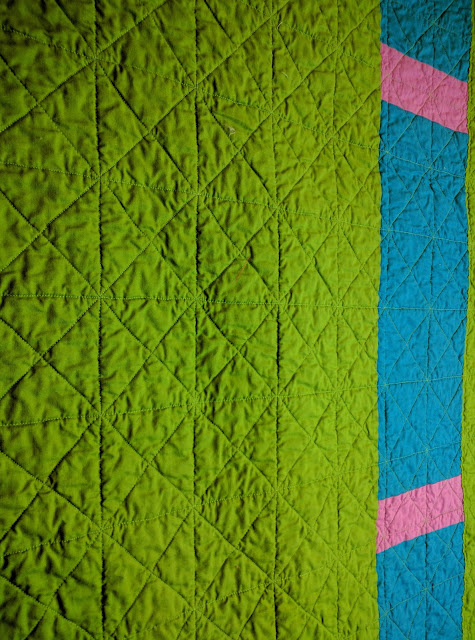 The stitch-in-the-ditch quilting shows on the green quilt back, diamonds and squares of stitches.