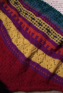 Textured section in red followed by sections of mosaic knitting and stripes in orange, yellow, green, blue, indigo, and purple. There is a lace section, knit in yellow as well.