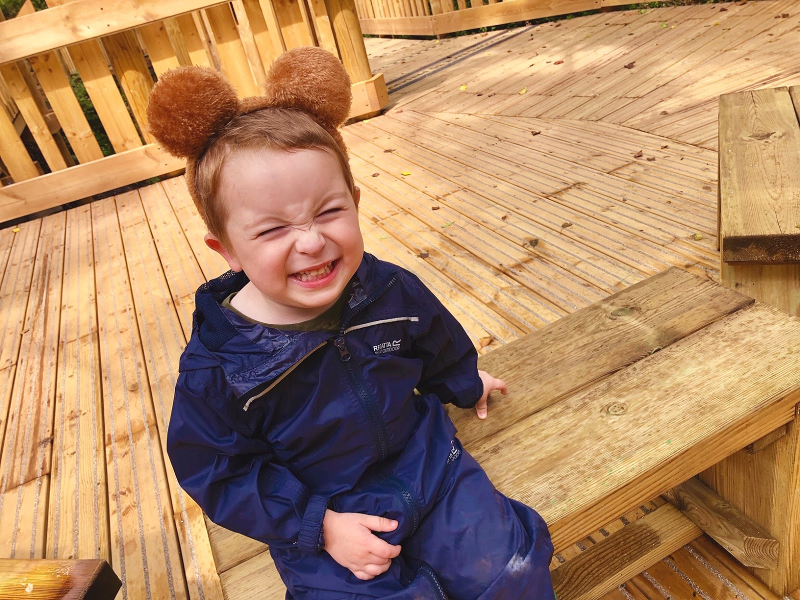 a toddler boy smiling and wearing a puddle suit and bear ears on his head