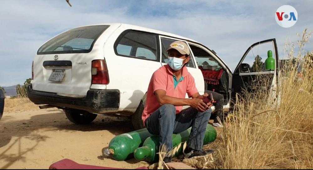 Un boliviano esperando con sus cilindros de oxígeno afuera de la planta de producción en Cochabamba, Bolivia, el 2 de junio de 2021 / VOA /Fabiola Chambi