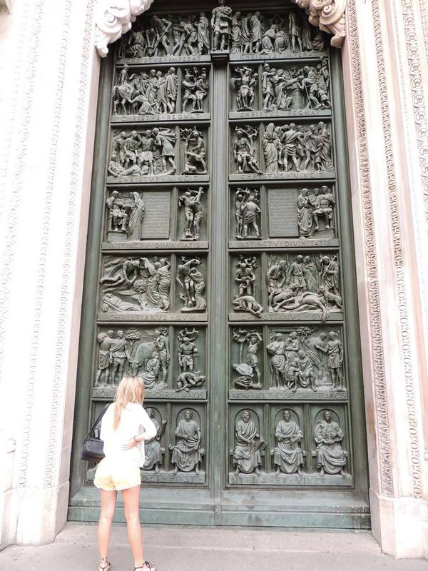 photo of visitor at bronze door of Duomo di Milano cathedral showing Emperors Constantine on left and Licinius on right, co-authors of the Edict of Milan