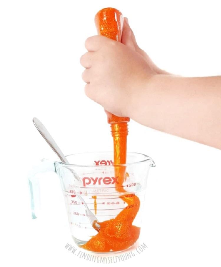pouring glitter glue into sensory bottle mixture