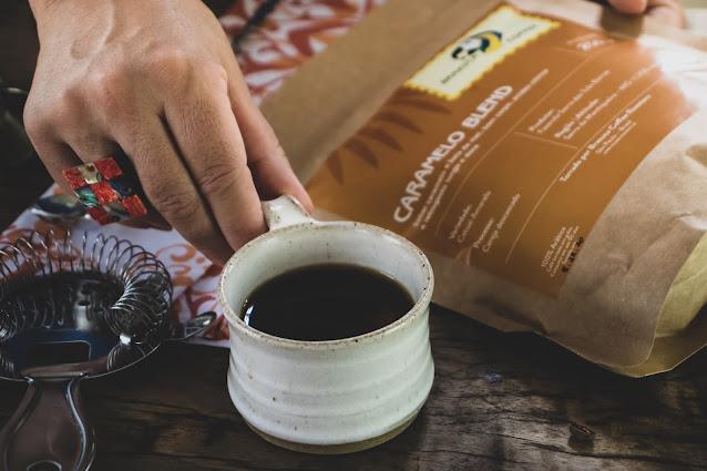 Xícara de café sendo segurada por mão feminina