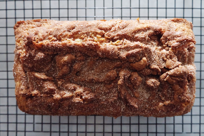 baked cinnamon  bread loaf cooling on rack