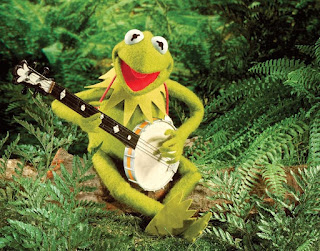 Kermit the Frog sitting in a forest with his banjo.