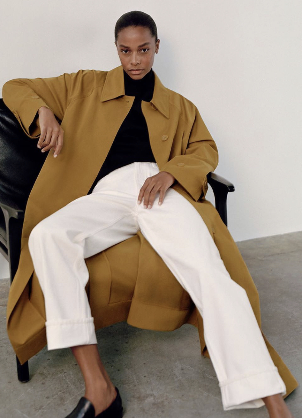 5 Minimalist Fall Outfit Ideas — Capsule Wardrobe with camel trench coat, black top, white jeans, and black loafers