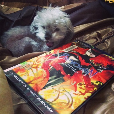 Murchie lies on a bronze comforter, his mouth stretched open in a yawn that looks a little like a roar and a little like a grin. Beside him is a hardcover copy of Batwoman Volume 3. Its cover features a redhaired white woman in a skintight black bat costume with red accents. Flames surround her.