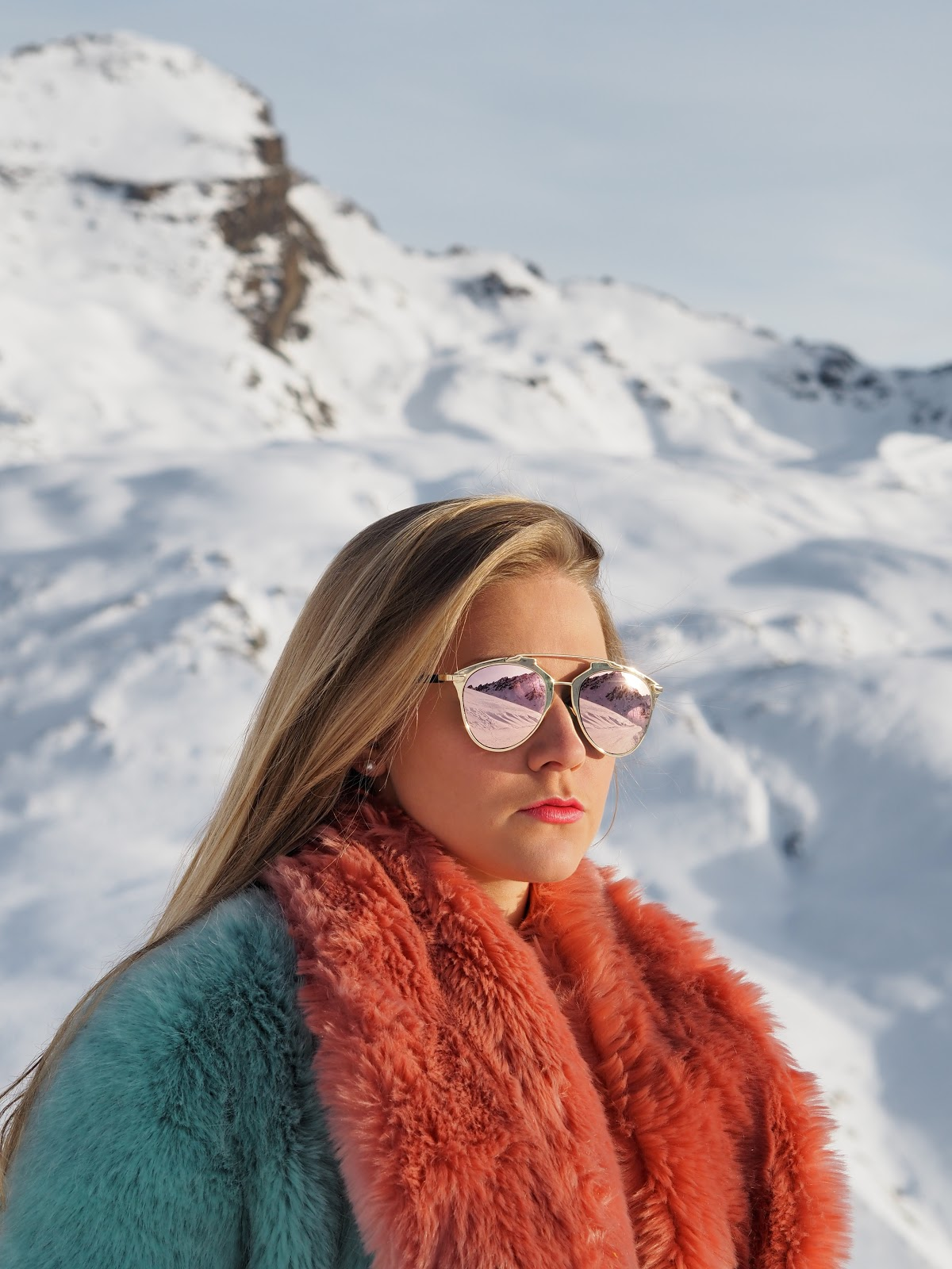 Blonde girl sitting in snowy mountains wearing blue and pink fur and sunglasses, Val d'Isere, France