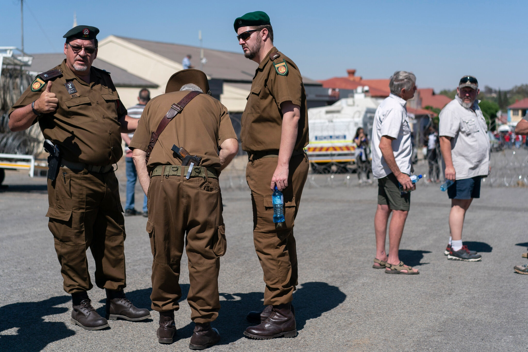Farmers wearing old South African Army uniforms outside the court.Credit...Joao Silva/The New York Times