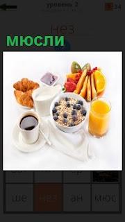 На белой поверхности чашка с кофе, сок желтого цвета, чаша с приготовленной едой и внутри мюсли