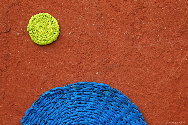 A Minimalist Photograph of a Yellow Circle and Blue Semicircle placed on a brown textured wall at Jawahar Kala Kendra, Jaipur.
