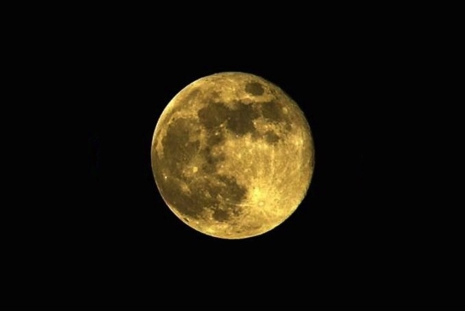 a golden full moon in a cloudless pitch-black sky