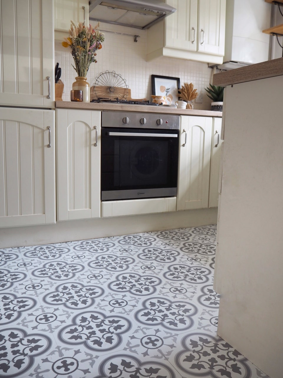 How to lay self-adhesive pell and stick vinyl floor tiles from Wall and Floor Pops. Simple budget DIY tutorial to revamp an old floor and give your home a budget makeover. Featuring exactly how I laid vinyl Floor Pops in the Remy pattern in our kitchen. Budget DIY project that you can easily do yourself.