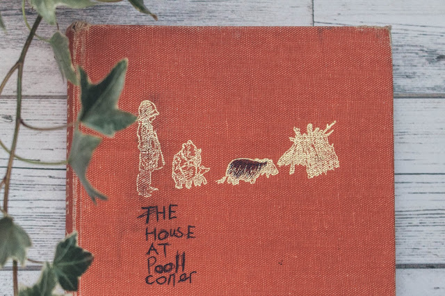 The House at Pooh Corner by A.A Milne surrounded by ivy.