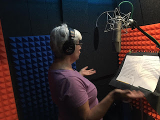 "We see Yvonne Schwemmer, voice over actress, in the recording booth headphones on head, reading from Olivia Ostergaard's book ""Looking at the Unseen."