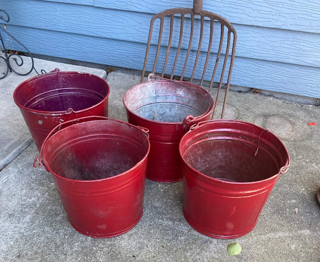 Photo of 4 galvanized buckets with red paint