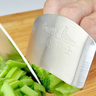 the buy in house finger guard amazon affiliate link, picture shows fingers safely inside the finger guard as vegetables are chopped with a knife