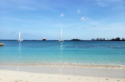 Anchored sailboats on calm sea.