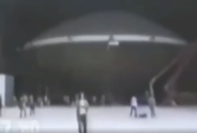 Lots of people stood in hangar and around aircraft hangar watching massive absolutely huge Flying Saucer while it's been moved.