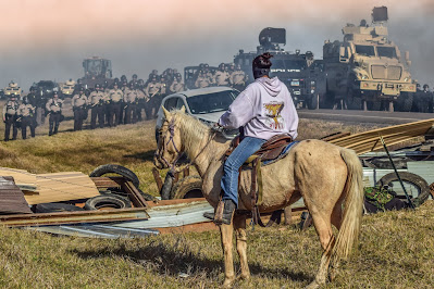 Rider on horse faces aremed law enforcement, Standing Rock protest, 2016
