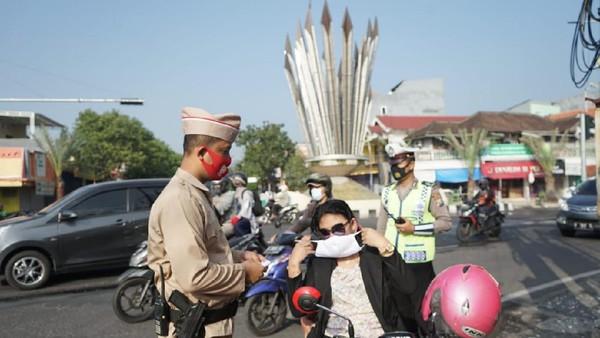 Kenakan Baju Pejuang, Polisi Bagikan Masker ke Warga Gresik