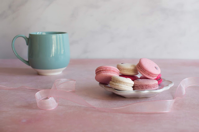 a plate of macarons and a large teal mug on a pink surface with a pink swirled ribbon