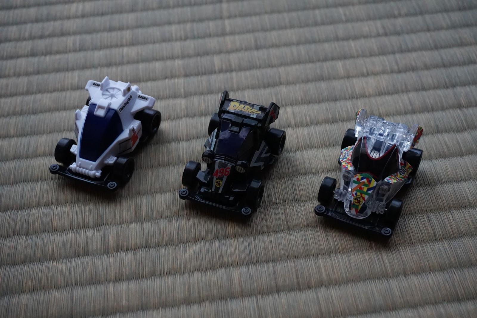 夕暮れ間近の畳の上の白と黒と透明の三台の小さなミニ四駆