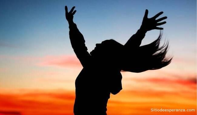Mujer feliz levanta las manos al cielo