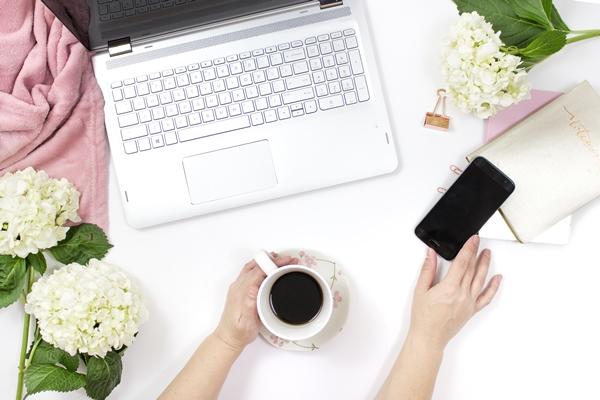 Flatlay mãos femininas segurando xícara de café enquanto pega o celular em frente ao notebook