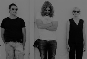 Publicity photo of Spiderbait with each member standing against a wall looking in various directions.