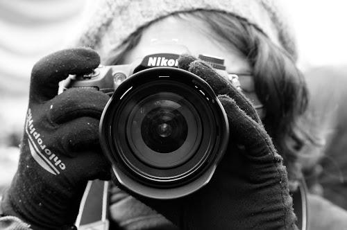 Fotógrafa de boina e luvas apontando sua câmera Nikon para o leitor