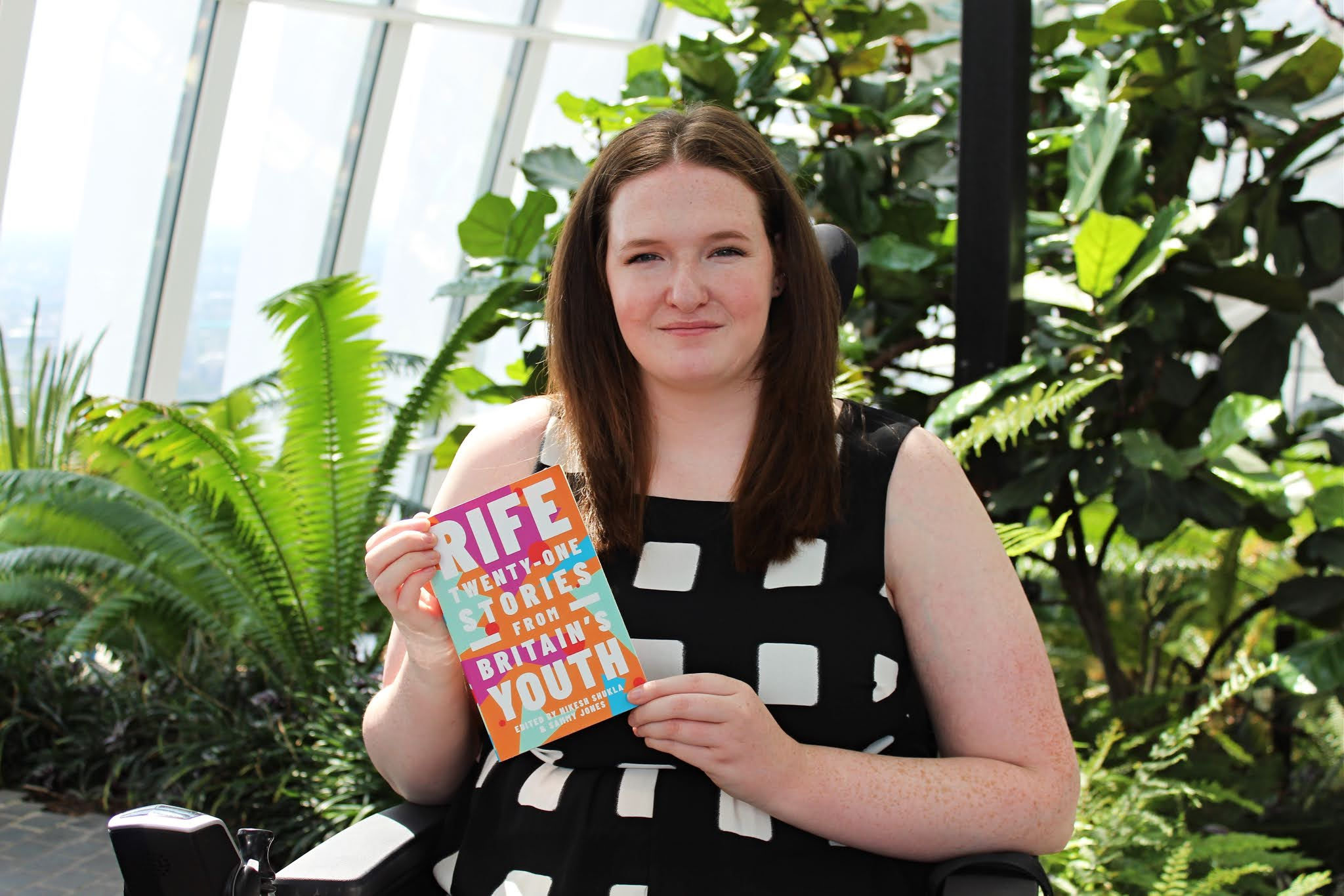 Shona, a young woman with long auburn hair, is sat in her powerchair wearing a black and white checkered jumpsuit. She is smiling and holding a brightly coloured book. Lots of green plants can be seen behind her. This photo was taken in the Sky Garden in London.