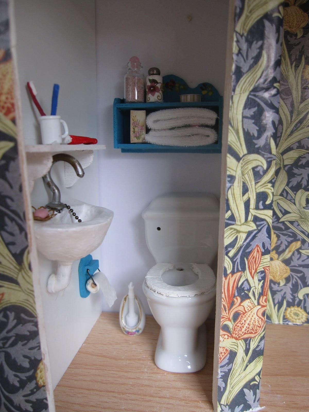 Och så toaletten  handfatet är gjort av fimolera med en silvermålad krok  som kran och en kedja ner till proppen. Hylla och toapappershållare är  byggda av ... c6f567cb1fc65