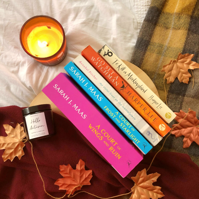 Stack of books with spines facing upwards next to fake autumn leaves and a 'Hello Autumn' candle