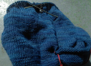 A sweater on circular needles, resting overtop of a yarn bowl.  There are live stitches kept out of the stocking stitch-work and held on a scrap of red yarn.  At the top, a shell-and-purl stitch marker is looped over the needle.