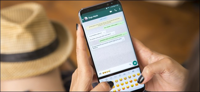 يد امرأة تحمل هاتفًا ذكيًا وتكتب الرموز التعبيرية في WhatsApp.